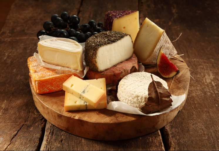 Assorted cheeses on a rustic wooden board